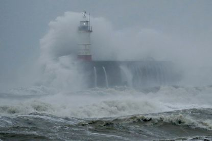 Waves crash over the harbour and a lighthouse as Storm Ciara hits Newhaven, on the south coast of England on Feb. 9, 2020.