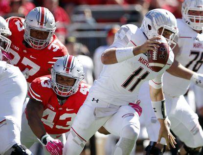Maryland quarterback Perry Hills (11) gets away from Ohio State linebacker Darron Lee (43) on a busted play during the first quarter on Saturday, Oct. 10, 2015, at Ohio Stadium in Columbus, Ohio. The host Buckeyes won, 49-28.