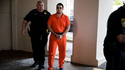 A law enforcement official escorts Cosmo DiNardo to a vehicle Thursday in Doylestown, Pa. Lawyer Paul Lang, a defense attorney for DiNardo, said Thursday that his client has admitted