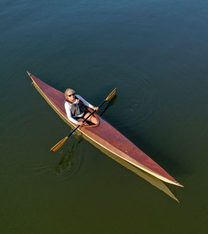 Kasia Taylor paddles off her community beach in Severna Park in a wooden kayak built for her by her husband Jay Taylor.