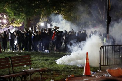 Tear gas billows as demonstrators gather in Lafayette Park to protest the death of George Floyd, Sunday, May 31, 2020, near the White House in Washington.