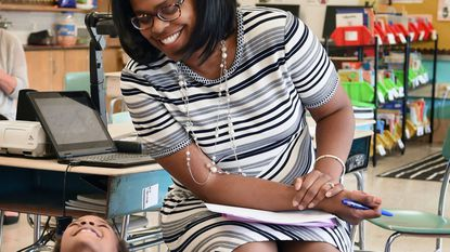 Baltimore schools CEO Sonja Santelises, top, shares laugh with a kindergartner at Calvin M. Rodwell Elementary during visit to the school with her leadership team.