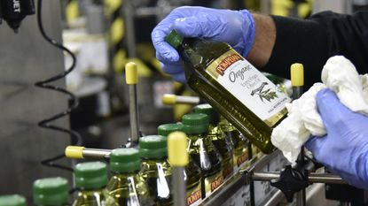 A worker at Pompeian Olive Oil Co. in Baltimore holds a bottle of Organic Extra Virgin Olive Oil in this 2015 file photo.