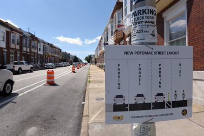 A sign notes the modifications being made along Potomac Street to accommodate two lanes of parking, a travel and bike lane.