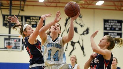 C. Milton Wright's Courtney Frank goes strong to the basket as Bel Air's Grace Wehland, left, and Autumn Dougherty, right, close in hoping for the block during Wednesday night's game at C. Milton Wright.