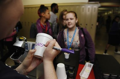 "On left, Barista Laura Hubbard, 17, Dundalk, a junior at Patapsco High School and Center for the Arts, writes ""Jules"" on a cup as Julia Lachnit, 17, Parkville, a senior, waits for her coffee."