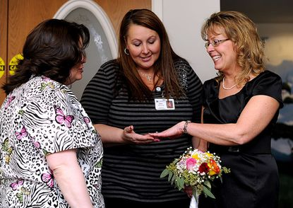 Lora Burns shows her wedding ring to co-workers Regina Colson, left, and Kathy Goad after being married in the chapel at Carroll Hospital Center in Westminster Valentine's Day, Feb. 14.