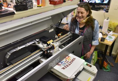 "Gaby Frank, printing one of the custom Havre de Grace Strong 2020 t-shirts that she prints at her business, Stickdesign Embroidery & Garment Printing Studio. The logo was designed by Paula Casagrande of Big House Designs. She has had the business for twenty years. (Editors: note that she prefers to be called ""Gaby,"" not Gabriele.) May 12, 2020"