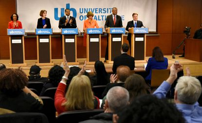 With four months to go until Baltimore's primary, mayoral candidate and City Council President Brandon Scott is proposing nine debates and forums. In 2016, the six candidates and audience applaud just before the start of a Democratic mayoral debate at the University of Baltimore.
