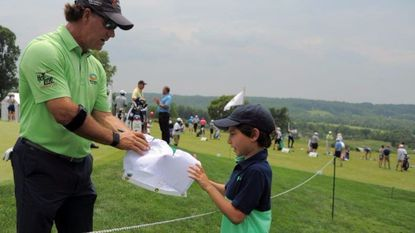 Drew Politziner, 7 of Palm Beach, Fla., gets an autograph from Scott McCarron, who just finished at the practice green during the 2017 Senior Players Pro Am at Caves Valley Golf Club.