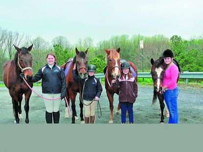 Members of the Glen Hollow Pony Club stand with their horses prior to a March 25 horse show. From left: Daisy and Dani Fox, Chrissy and Morgan McGrain, Thunder and Allison Stoner, Princess and Casey Bounds.