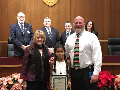 Marleigh Skelton, center, a student at Homestead-Wakefield Elementary School, received a Student Achievement Award from Bel Air Mayor Susan Burdette, left, and the rest of the Board of Town Commissioners on Dec. 18. H-WES Principal Chris Cook, right, joined her for the occasion. - Original Credit: