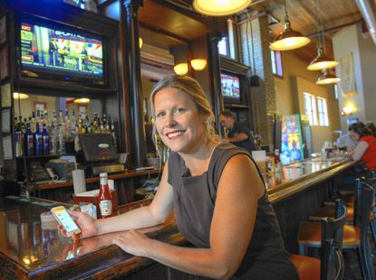 """Howard County Tourism and Promotion's Amanda Hof, shows off a new app called """"Howard on Tap."""" It encourages people to go on a virtual beer trail tour of the county's breweries. She's at the Ellicott Mills Brewing Co., the county's first brewery-restaurant."""