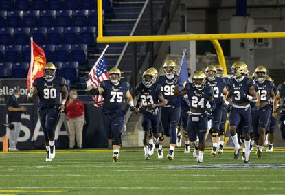 Navy football players take the field before its season-opening game against BYU on Labor Day. The Midshipmen take on Tulane Saturday in their first road game.