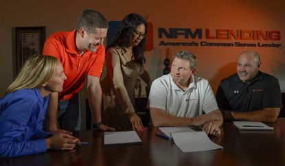 At NFM Lending in Linthicum, (L-R) HR Director Bernadette Pearson, Capital Markets Director Tom Sealock, General Counsel LaTasha Rowe, Director of Operations Shaun Hires, and CFO Matthew Glyder, gather around gather in the conference room there