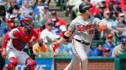 Rangers catcher Robinson Chirinos, left, watches as Orioles first baseman Chris Davis follows through on a run-scoring single in the fourth inning Sunday.