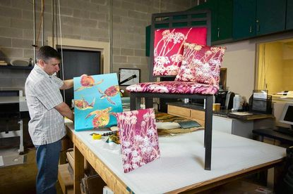 Jeff Salava, founder of Hot Boltz, shows off some pieces in his Arbutus shop. The Catonsville resident uses on-textile printing technology that incorporates a dye-sub process to transfer works of art onto fabric. He is scheduled to have his work on display during Sunday's 40th annual Catonsville Arts and Crafts Festival.