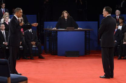President Barack Obama (L) speaks as Republican presidential candidate Mitt Romney (R) and moderator Candy Crowley (C) listen during a town hall style debate at Hofstra University October 16, 2012 in Hempstead, New York. During the second of three presidential debates, the candidates fielded questions from audience members on a wide variety of issues.