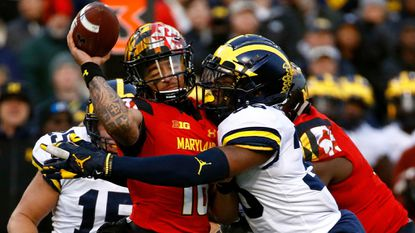 Michigan linebacker Josh Uche, right, tackles Maryland quarterback Ryan Brand as Brand throws an incomplete pass in the first half of a game in College Park on Saturday, Nov. 11, 2017.