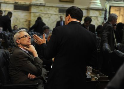 Del. A. Wade Kach, left, a Baltimore County Republican, listens to Del. Ron George before the start of the session Thursday on the floor of the House of Delegates.