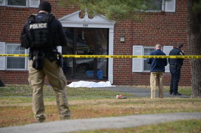 Baltimore Police investigate a crime scene which appears to show a body covered under a white sheet outside of an apartment in Northeast.
