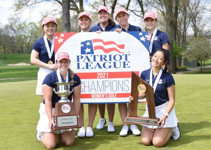 Coach Nadia Ste-Marie (back row, middle) and members of the Navy women's golf team display the hardware earned from capturing their first Patriot League championship.