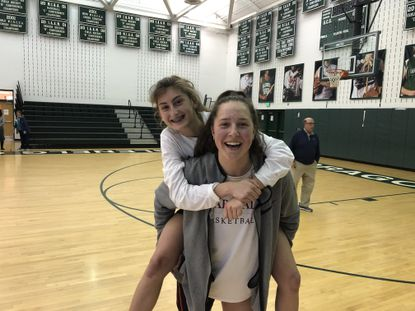 Maryvale's Claire Neff (front) gives Emily Knapp (back) a piggyback ride after their 58-42 victory over Glenelg Country in the IAAM B Conference quarterfinals.