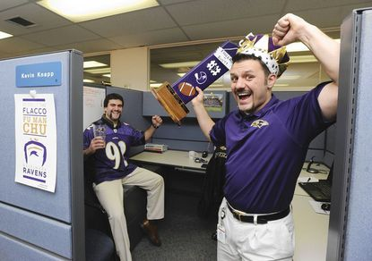 Employees at Roadnet Technologies have the Ravens spirit. At left is Evan Varipatis. At right is Kevin Knapp, who's holding the fantasy football league trophy.