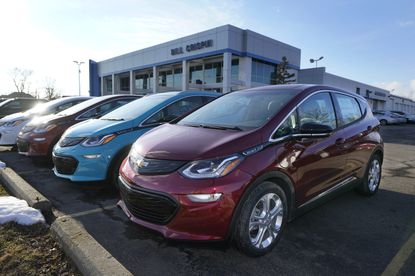 A 2021 Chevrolet Bolt EV, is displayed with 2020 models at Bill Crispin Chevrolet Thursday, Feb. 25, 2021, in Saline, Mich. Opinion polls show that most Americans would consider an EV if it cost less, there were more charging stations along freeways and if automakers offered a bigger variety of models. (AP Photo/Carlos Osorio)