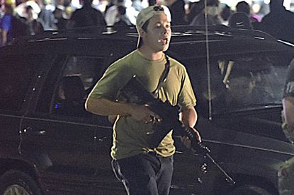 Kyle Rittenhouse carries a weapon as he walks along Sheridan Road in Kenosha, Wis., during a night of unrest following the weekend police shooting of Jacob Blake on Aug. 25, 2020.
