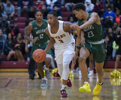New Town's Martaz Robinson dribbles down the court, defended by Milford Mill's Trevon Gwaltney.