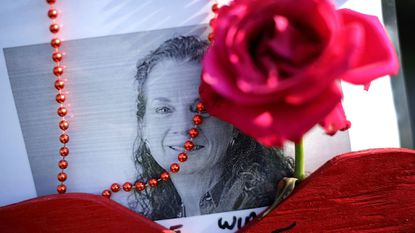 Beads, a wooden heart and flowers decorate a photograph of Wendi Winters at a makeshift memorial outside the Capital Gazette Communications offices. Winters was a long-time community columnist for The Capital. She was killed in a shooting at the newspaper's office June 28.