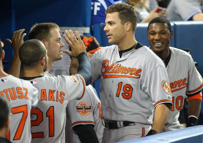Orioles first baseman Chris Davis is congratulated by teammates after hitting a two-run home run in the fourth inning Saturday in Toronto.