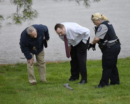 Police look at a rifle left in the grass at the scene of a police-involved shooting behind a business in the unit block of East Green Street near the Maryland Midland Railway tracks in Westminster Friday evening, April 3, 2020.