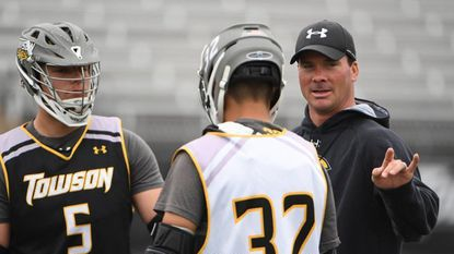 Steven Stillwell (No. 5) and Alec Burckley listen as Towson coach Shawn Nadelen works with players on the faceoff.