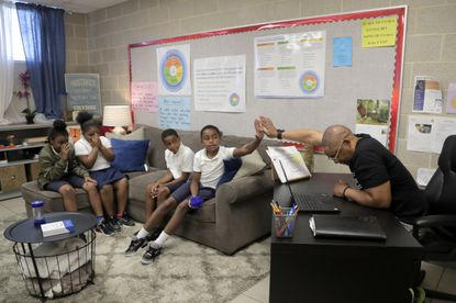 """In a photo taken Tuesday, July 2, 2019, Scott Hopewell, right, a student holistic specialist, gives a high-five to a child during a group session in a """"peace room"""" at New Song Community Learning Center in West Baltimore. In Baltimore, there's been a growing realization that levels of youthful trauma, whether exposure is mostly from neighborhood or domestic dysfunctions, are alarmingly high."""