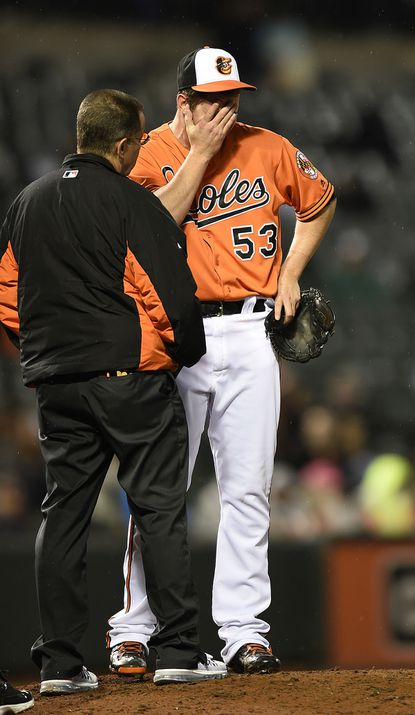 Baltimore Orioles pitcher Zach Britton talks with trainer Richie Bancells after injuring his ankle reaching for a bunt by the Chicago White Sox during the ninth inning of a baseball game, Saturday, April 30, 2016, in Baltimore. The White Sox won 8-7.