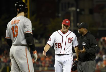Washington Nationals relief pitcher Jonathan Papelbon (58) reacts next to umpire Alan Porter (64) during the ninth inning of an interleague baseball game, Wednesday, Sept. 23, 2015, in Washington. Papelbon was ejected for hitting Baltimore Orioles' Manny Machado with a pitch. Also seen is Baltimore Orioles' Chris Davis (19). The Orioles won 4-3.
