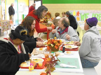 Lois Giles, who has volunteered with Shepherd's Staff for 22 years, talks with Harry Turner as he eats a Thanksgiving meal Thursday, Nov. 27 in Westminster.