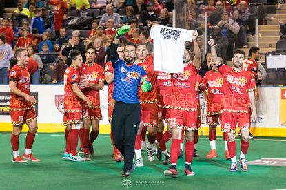 """Goalkeeper William Vanzela waves to the crowd as Blast players hold up a """"Be Strong"""" T-shirt for defender Elton de Oliveira, whose father died earlier this week."""