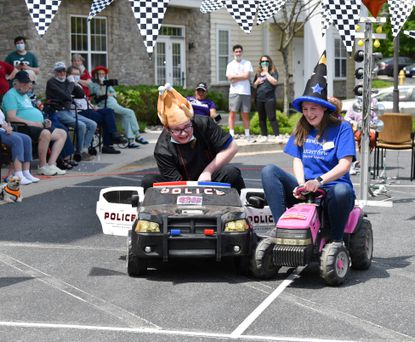 Brightview Avondell employee Destiny Schott, right, tries to sabotage fellow employee Evan Greco's win as the pair comes to the finishline in the drag race to raise money for the Alzheimer's Association Wednesday April, 28, 2021. The race, along with raffles and donations from local businesses, raised over $2500 to be donated to the Alzheimer's Association.