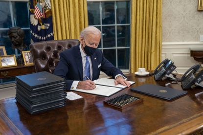 President Joe Biden signs executive orders during his first minutes in the Oval Office of the White House in Washington, on Inauguration Day, Wednesday, Jan. 20, 2021.