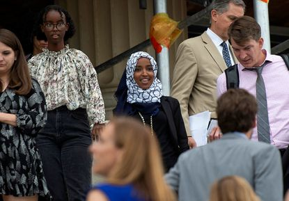 """Rep. Ilhan Omar, D-Minn., center, walks down the steps of the Capitol on July 16, 2019, in Washington D.C. after the House of Representatives, with a Democratic majority, passed a resolution along largely party lines with 235 Democrats and only four Republicans voting for the nonbinding resolution that """"... condemns President Donald Trump's racist comments that have legitimized and increased fear and hatred of new Americans and people of color by saying that our fellow Americans who are immigrants, and those who may look to the President like immigrants, should """"go back"""" to other countries, by referring to immigrants and asylum seekers as """"invaders,"""" and by saying that Members of Congress who are immigrants (or those of our colleagues who are wrongly assumed to be immigrants) do not belong in Congress or in the United States of America."""""""