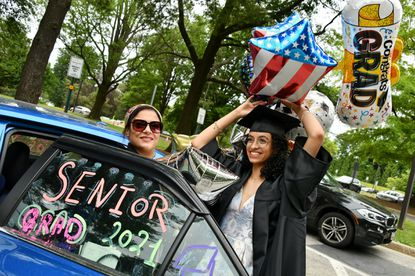Halla Ismail smiles as her father Wael Ismail takes photos of her and her mother, Mai Mohamed, with celebratory balloons and a decorated car after her graduation from Dulaney High School. Halla will be attending Towson University, where the graduation ceremony took place at SECU Arena.