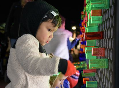 Daniel Lopez, plays with light pegs. Light City opening night in Baltimore. Photo by Ulysses Muñoz, Baltimore Sun