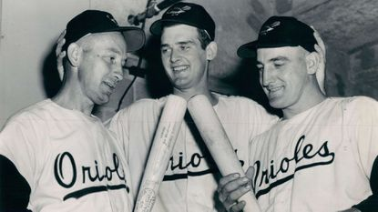 May 31, 1954 - WON BY THREE -- Eddie Waitkus (left) and Jim Fridley (right) eye bats which produced timely homers for Don Larsen (center), who hurled the Orioles to victory over White Sox.