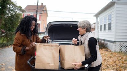 Lisa Louis, left, and volunteer Bonnie Wilson, right, both of Catonsville share a laugh while they load bags of food outside of Catonsville Emergency Assistance on Nov. 14, 2017. A grant from the Catonsville Women's Giving Circle will let the organization buy more sturdy bags.