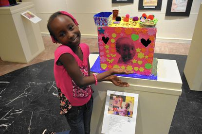"""Maisa Ibrahim, 8, originally from South Sudan, poses with her art at the """"Sanctuary"""" exhibition at Baltimore City Hall."""