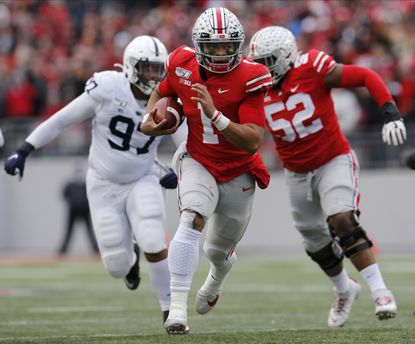 Ohio State quarterback Justin Fields runs for a first down against Penn State during the first half Saturday, Nov. 23, 2019, in Columbus, Ohio.