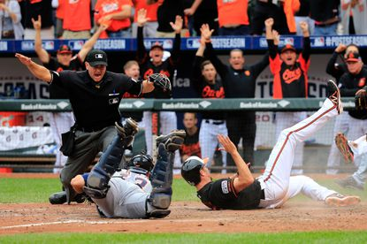 Baltimore's J.J. Hardy, right, is one of three runners to score off an eighth-inning double by Delmon Young as the Orioles rally to take Game 2 of their ALDS game against Detroit.
